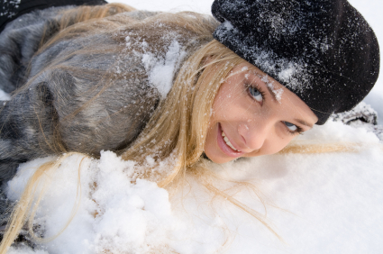 A girl smiling, laying on the snow